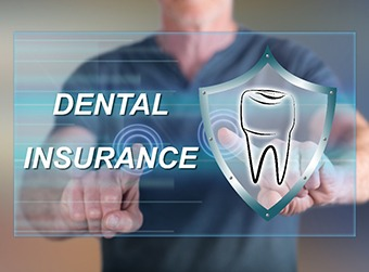 "A dentist standing behind an image that reads ""Dental Insurance"" and has a tooth next to it"