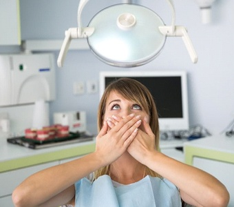 A woman covering her mouth in the dental chair.