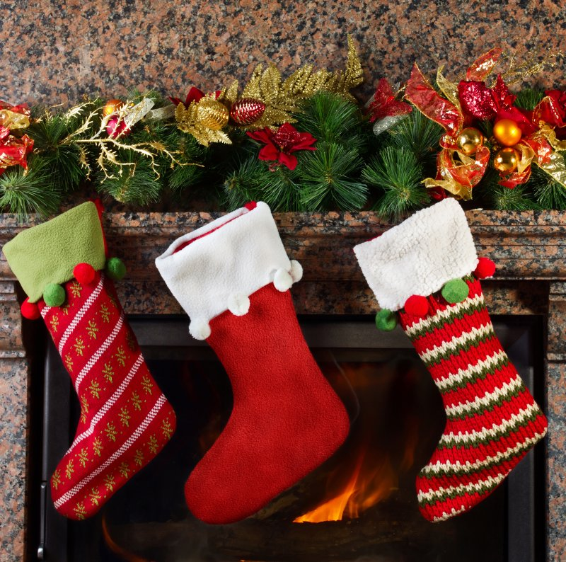 an image of three holiday stockings hung on the mantle
