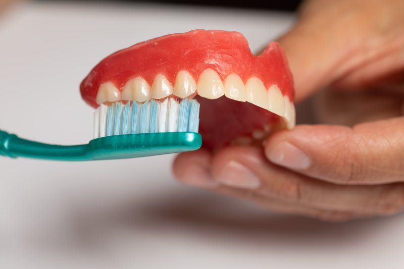 Falmouth patient cleaning dentures with toothbrush