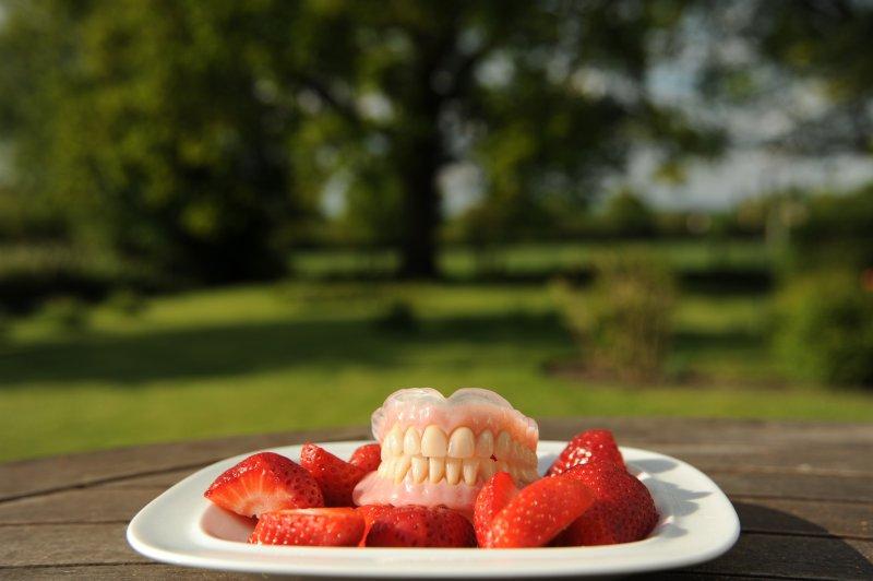 dentures on plate of strawberries